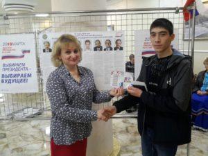 Впервые принявший участие в выборах Михаил получает поздравление от участков избирательном комиссии